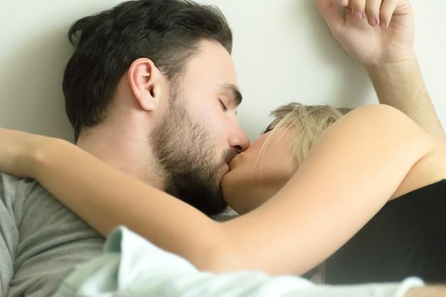 Miłości para całuje w łóżku. szczęśliwa para leżąc razem w łóżku.