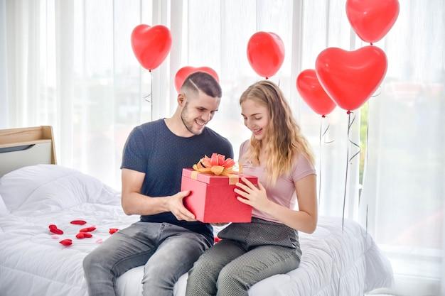 Miłości para daje prezenta pudełku w sypialni szczęściu w miłości walentynki pojęciu