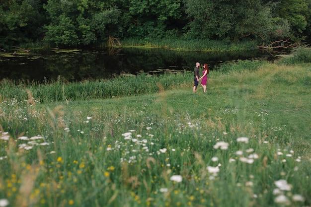 Miłości para na zielonym polu. uy i dziewczyna spaceru i przytulanie w zielonym ogrodzie na świeżym powietrzu