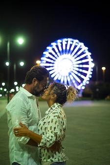 Miłości para obejmując się i całując się na ulicy w nocy. para romansuje i spędza czas na świeżym powietrzu. czule para całuje się z podświetlanym tłem diabelskiego młyna w nocy