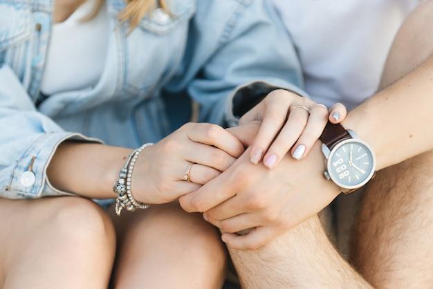 Miłości para trzymając się za ręce, siedząc na piasku z bliska rąk