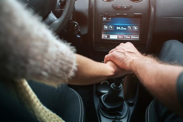 Miłości para trzymając się za ręce w samochodzie. jesień jesienna leśna podróż samochodem.