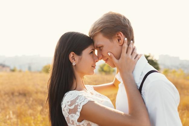 Miłości para ubrana na biało całuje na zewnątrz