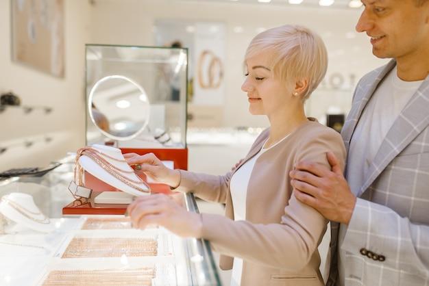 Miłości para wybiera złoty łańcuch. klienci płci męskiej i żeńskiej patrząc na biżuterię w sklepie jubilerskim. mężczyzna i kobieta kupują złotą dekorację. przyszła panna młoda i pan młody w sklepie jubilerskim