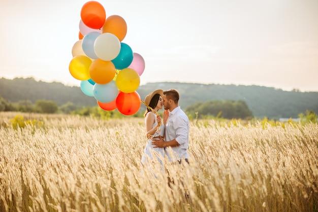 Miłości para z balonami przytula w polu żyta