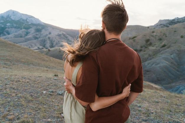 Miłośnicy cieszą się zachodem słońca. facet i dziewczyna stoją i przytulają się. romantyczna randka na szczycie góry. walentynki obchodzone są przez zakochanych.