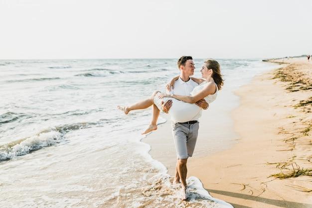 Miłośnicy nad oceanem przytulają się i bawią. mąż i żona przytula się o zachodzie słońca w pobliżu morza. kochankowie na wakacjach. letni odpoczynek. romantyczny spacer nad oceanem