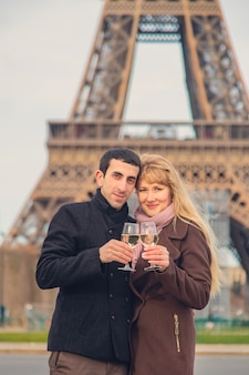 Miłośnicy piją wino w pobliżu wieży eiffla w paryżu. selektywne ustawianie ostrości.