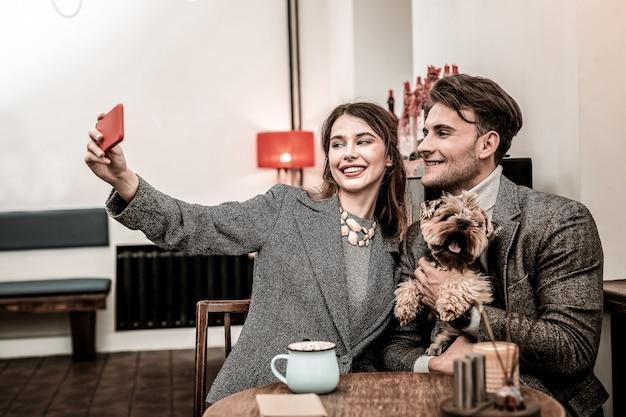 Miłośnicy selfie. kobieta robi selfie ze swoim partnerem i psem