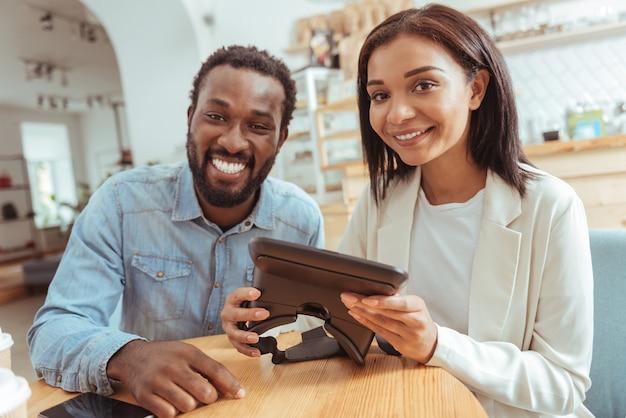 Miłośnicy technologii. przyjemni, radośni najlepsi przyjaciele siedzą w kawiarni, trzymając gogle vr i szeroko uśmiechając się do kamery