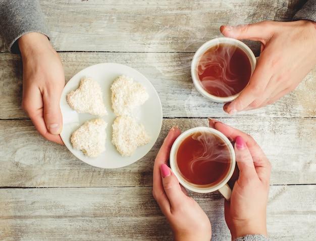 Miłośnicy trzymając razem filiżankę herbaty. selektywna ostrość.