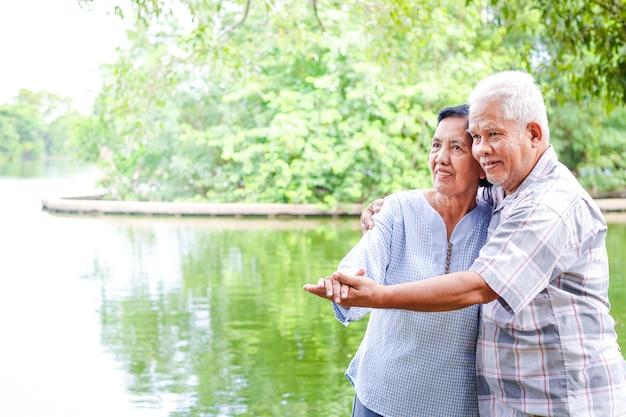 Miłośnicy w podeszłym wieku trzymając się za ręce tańczą w ogrodzie baw się dobrze na emeryturze. koncepcje społeczności seniorów