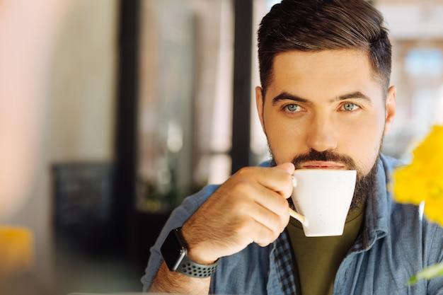 Miłośnik kawy. portret przystojnego brunetki podczas picia pysznej kawy