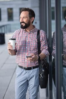 Miłośnik kawy. wesoły brodaty mężczyzna pije kawę stojąc w pobliżu budynku biurowego