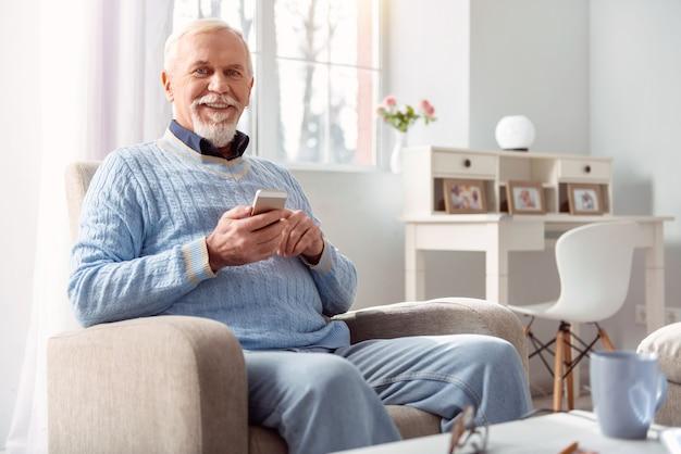 Miłośnik mediów społecznościowych. uroczy, optymistyczny starszy mężczyzna siedzący w fotelu i uśmiechając się przewijając oś czasu swoich mediów społecznościowych