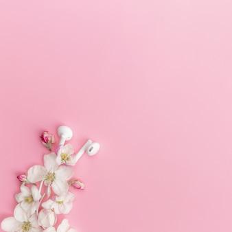 Miłośnik muzyki lub koncepcja świeżej muzyki mieszkanie leżało na różowym tle z kwiatem jabłoni i białymi słuchawkami. zdjęcie wysokiej jakości