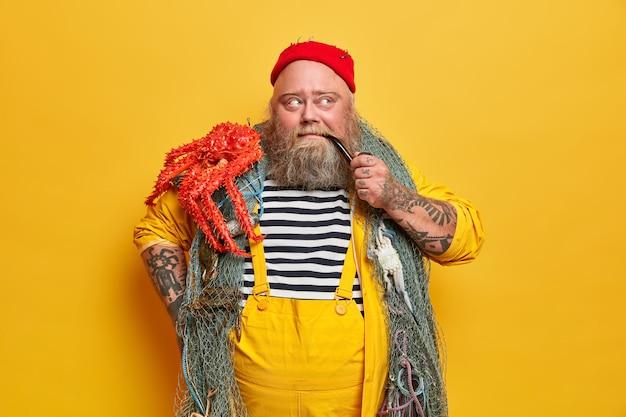 Miłośnik wędkowania złapał ośmiornicę w morzu lub oceanie, pali fajkę i myśli o planach na przyszłość, ma gęstą brodę