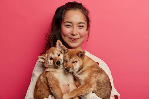 Miłośnik zwierząt domowych i przyjaźń z koncepcją właściciela. azjatka bawi się dwoma rodowodowymi małymi psami, wolny czas lubi spędzać ze zwierzętami domowymi