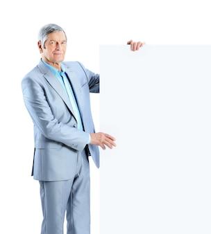 Miły biznesmen posiada biały plakat. pojedynczo na białym tle.