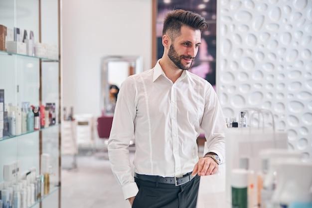 Miły brodaty mężczyzna oparty na stole, stojąc w pobliżu recepcji