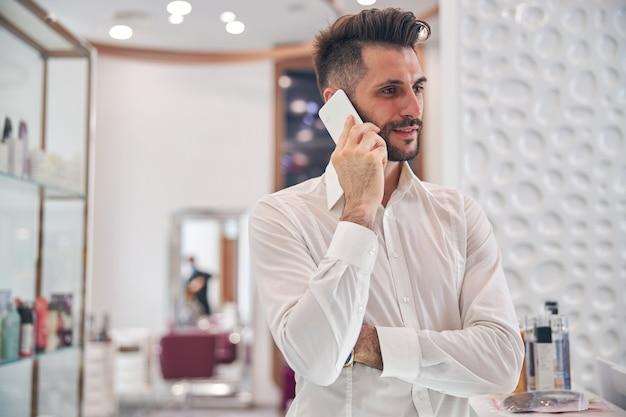 Miły brodaty mężczyzna stojący na pierwszym planie i trzymający uśmiech na twarzy podczas rozmowy telefonicznej