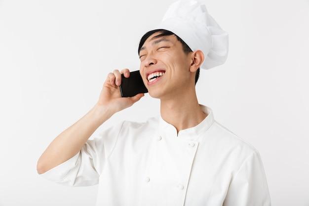 Miły chiński wódz w białym mundurze kucharza i kapelusz szefa kuchni rozmawia przez telefon komórkowy na białym tle nad białą ścianą