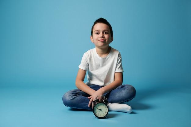 Miły chłopak ubrany w białą koszulkę i dżinsy, siedząc na niebieskiej powierzchni z kopią miejsca za budzikiem