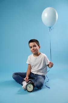 Miły chłopak uśmiecha się, siedząc obok budzika na niebieskiej powierzchni i trzymając niebieski balon