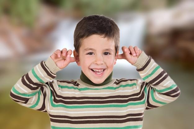 Miły chłopak zakrywający uszy