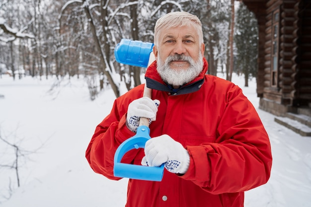 Miły człowiek patrząc na kamery podczas usuwania śniegu w okresie zimowym