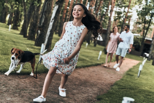 Miły dzień z rodziną. pełna długość uroczej małej dziewczynki z psem uśmiecha się podczas spaceru z rodzicami w parku