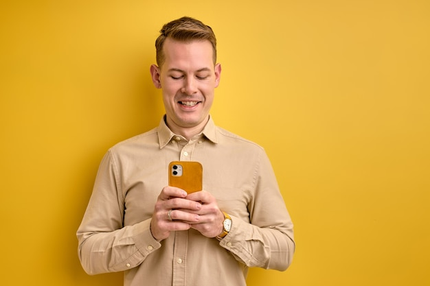Miły europejski mężczyzna trzyma smartfon w rękach tworząc myślenie influencer strategii społecznej