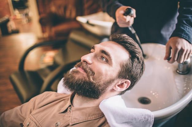 Miły facet dba o swoje włosy. fryzjer myje włosy. klient jest zrelaksowany i czuje się szczęśliwy.