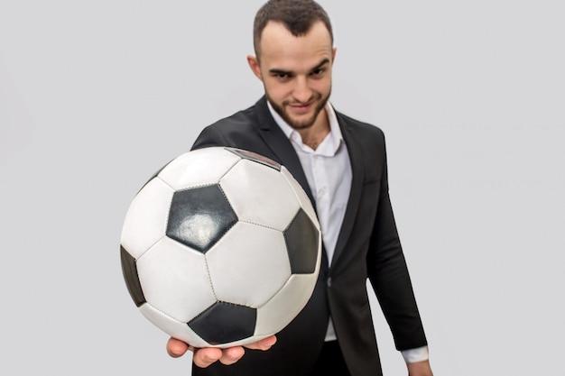 Miły i pewny siebie młody człowiek w garniturze trzyma piłkę do gry w piłkę nożną.