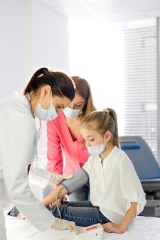 Miły lekarz sprawdzi ciśnienie krwi dziewczynki siedzącej na łóżku w masce, która przyszła z mamą. koronawirus (covid-19