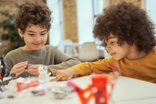 Miły mały chłopiec wyglądający radośnie, siedząc przy stole ze swoim przyjacielem i badając szczegóły