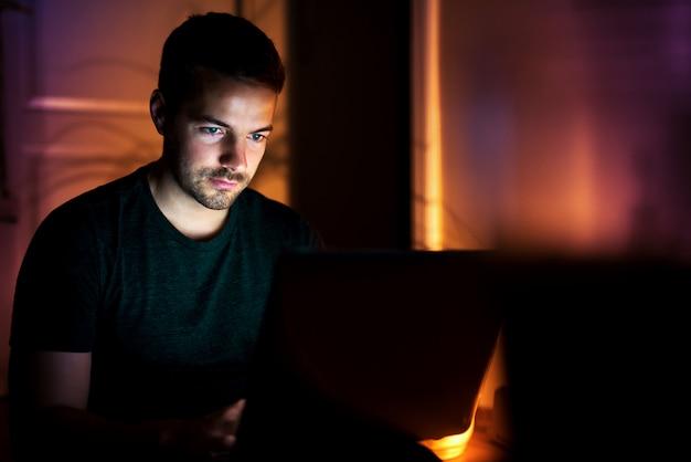 Miły mężczyzna rozmawia z przyjaciółmi siedząc na podłodze z laptopem