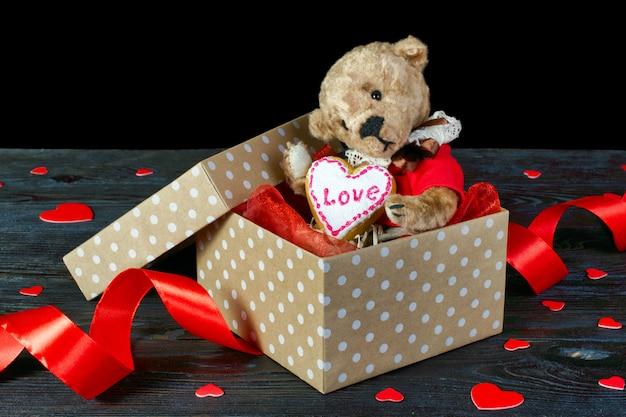 Miły miś siedzący w pudełku z sercem.