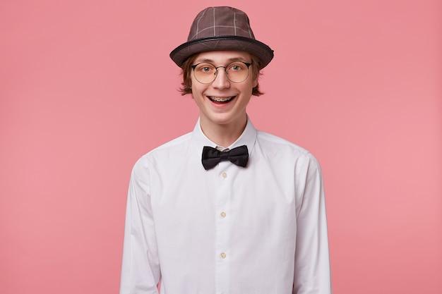 Miły młody chłopak w białej koszuli, kapeluszu i czarnej muszce nosi okulary radośnie szeroko uśmiechnięte, pokazując zamki ortodontyczne, odizolowane na różowym tle