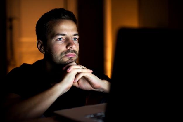 Miły młody człowiek ogląda filmy z rękami na brodzie