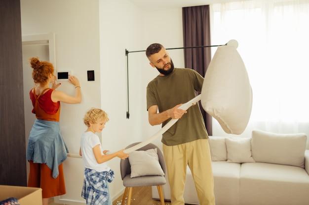 Miły młody człowiek trzymający poduszkę na sofie