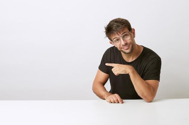 Miły młody człowiek w okularach skierowany w bok na białym biurku, oparty na białym biurku. ubrana w czarną koszulkę. prezentacja produktu.
