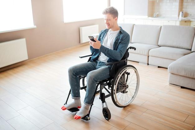 Miły młody człowiek z inkluzją i niepełnosprawnością. siedząc na wózku inwalidzkim. trzymając telefon w ręce i spójrz na niego. światło dzienne w dużym pustym pokoju.