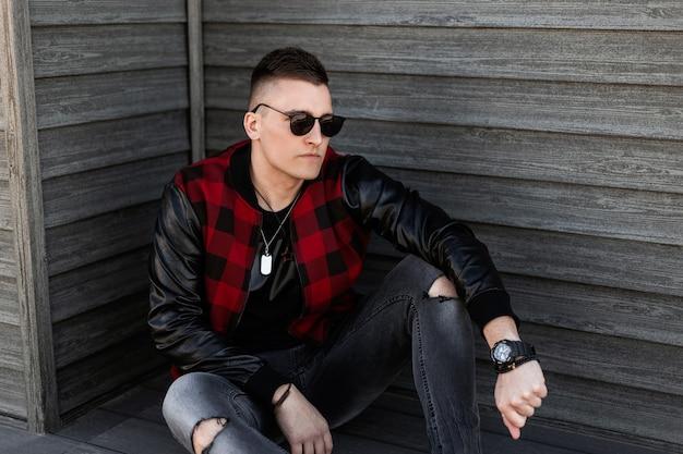Miły młody hipster mężczyzna w czarnych okularach przeciwsłonecznych ze stylową fryzurą w modnej czerwonej kraciastej kurtce w szarych podartych dżinsach siedzi na zewnątrz w pobliżu drewnianego budynku w letni dzień