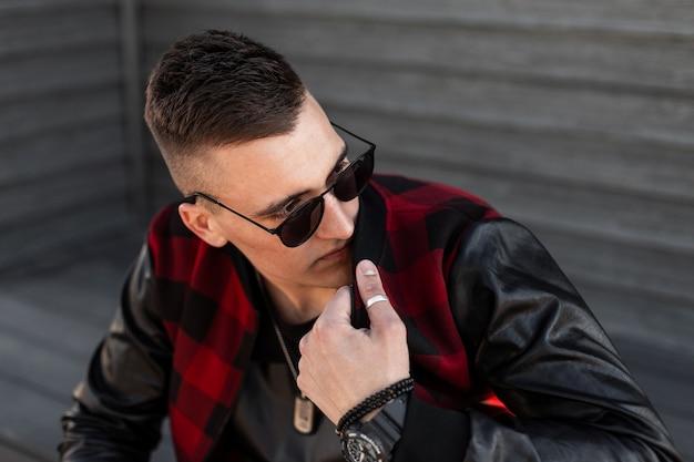 Miły młody hipster mężczyzna z fryzurą z czerwoną modną kurtką w kratę w czarnej koszulce ze stylowymi okularami przeciwsłonecznymi pozuje w pobliżu drewnianej ściany w stylu vintage