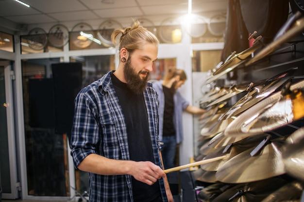 Miły młody hipster stoi na talerzach i dotyka ich pałeczkami. patrzy na nich. kolejny młody człowiek również się zachowuje i dotyka talerzy.
