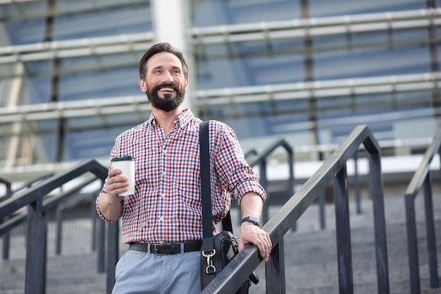 Miły początek dnia. wesoły, uśmiechnięty mężczyzna pije kawę podczas spaceru w środowisku miejskim