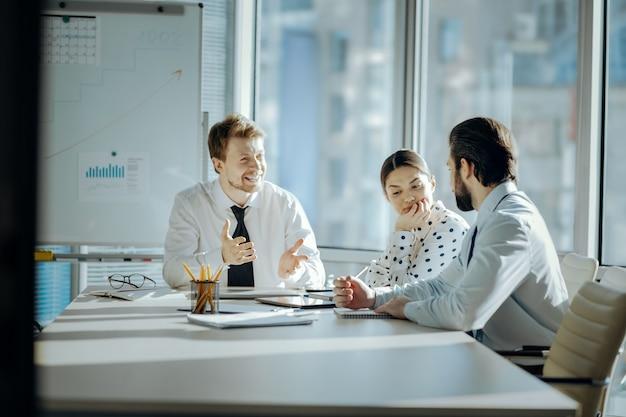 Miły początek dnia. żywiołowi młodzi koledzy siedzą przy stole i radośnie się śmieją, żartując podczas porannej odprawy