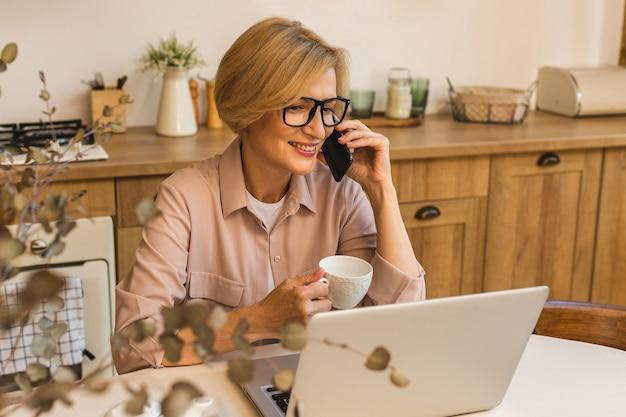 Miły poranek. wesoła uśmiechnięta starsza kobieta w wieku stojąca w kuchni i korzystająca z laptopa podczas odpoczynku po śniadaniu, freelancer pracujący w domu. korzystanie z telefonu komórkowego.