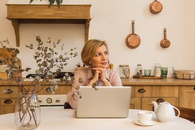 Miły poranek. wesoła uśmiechnięta starsza kobieta w wieku stojąca w kuchni i korzystająca z laptopa podczas odpoczynku po śniadaniu, pracująca w domu.